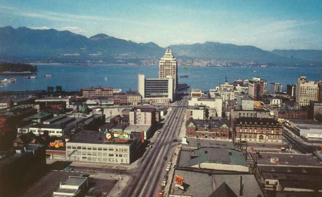 """The Customs and Marine Building on the waterfront at the north end of Vancouver's Burrard Street, stands majestic against the city's vibrant harbour. Notice how empty the now traffic clogged Burrard street was in the mid 1950s! According to the caption on the back of the card """"The North Shoreline Mountains are snow-covered most of the year and form excellent skiing grounds. Two electric ski lifts make this ski playground famed throughout the Northwest."""" (Postcard published by Vancouver Magazine Services LTD., Vancouver, B.C.)"""