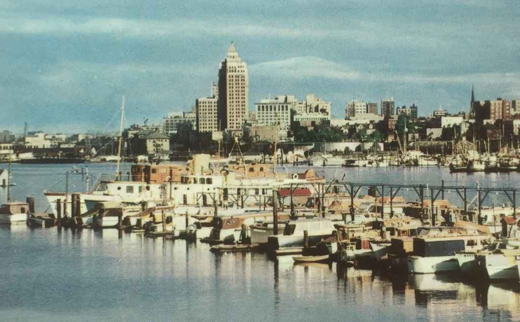 Vancouver Waterfront Coal Harbour as viewed from Stanley park circa 1954. In the foreground are boats belonging to the Burrard Yacht Club. In the background can be seen the prominent Marine Building, the then tallest building in Vancouver. (Postcard published by Vancouver Magazine Services LTD., Vancouver, B.C.)