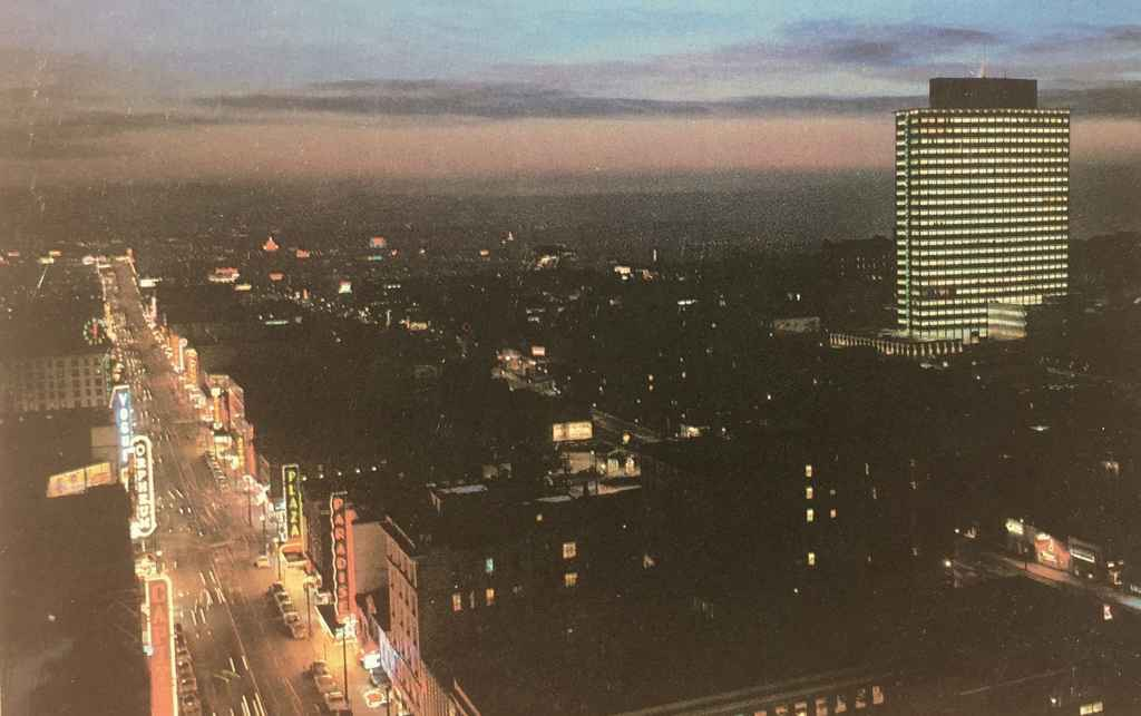Dusk view of Granville Street looking south and the then new BC Electric Building circa mid 1950s. The BC Electric building was the new head office for the Vancouver based electric utility company in a modern 21 story, 285 foot high structure. (Rolly Ford photo, postcard published by Natural Color Productions LTD., Vancouver, B.C.)