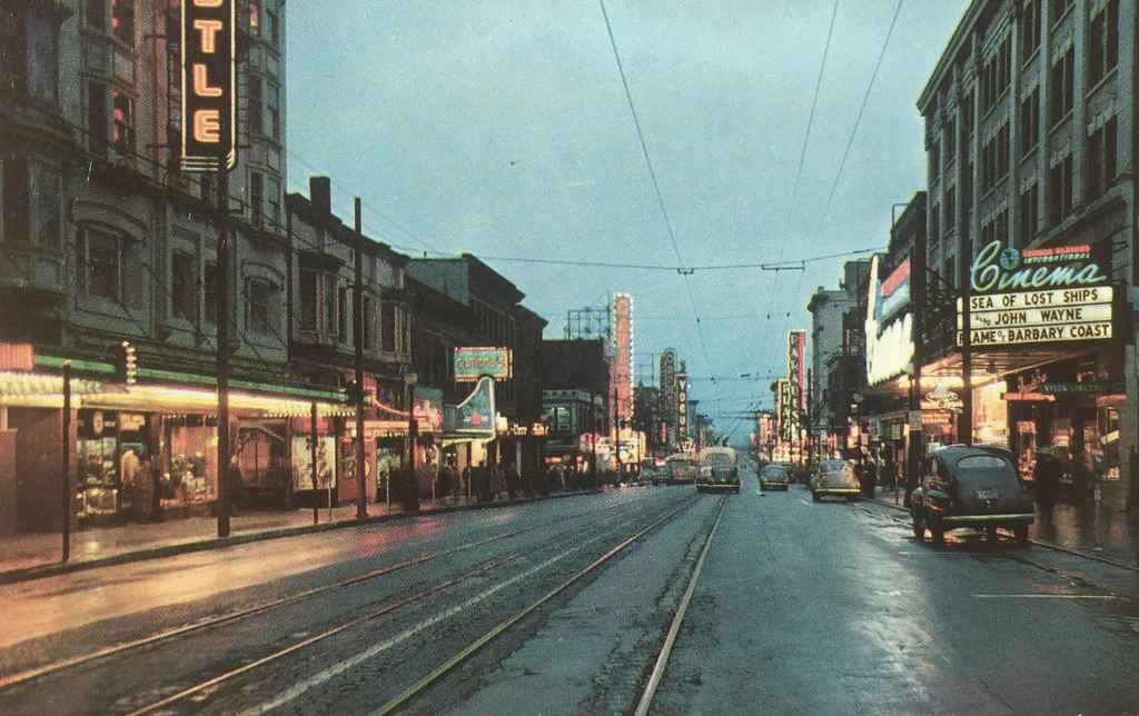 """Granville Street looking south from Georgia with the Capitol Theatre, Famous Players theatre, Parades Theatre and the Plaza Theatre. We can date this view to 1953, the year of theatrical release of """"Sea of Lost Ships"""" starring John Derek and Wanda Hendrix. (Published by Walker & Ward Scenic Cards LTD., Vancouver, BC, Canada)"""