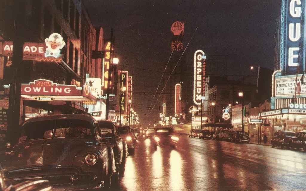 """Night scene of Vancouver, BC, Canada, showing a portion of the theatre district. Vancouver is known for its high concentration of neon in the downtown area. We can date this image to 1955, the year the film """"Above Us the Waves"""" staring John Mills was released theatrically. (Postcard published by Vancouver Magazine Services LTD., Vancouver, BC)"""