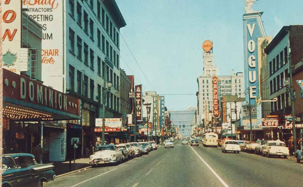 """Granville Street Vogue and Orpheum Theatres circa 1954. Granville is Vancouver's busiest and most colourful street, showing the heart of the city's vibrant theatre district, with its numerous neon signs. (Grant-Mann Lithographers LTD """"COLOR CARD"""" division, Vancouver, BC)"""